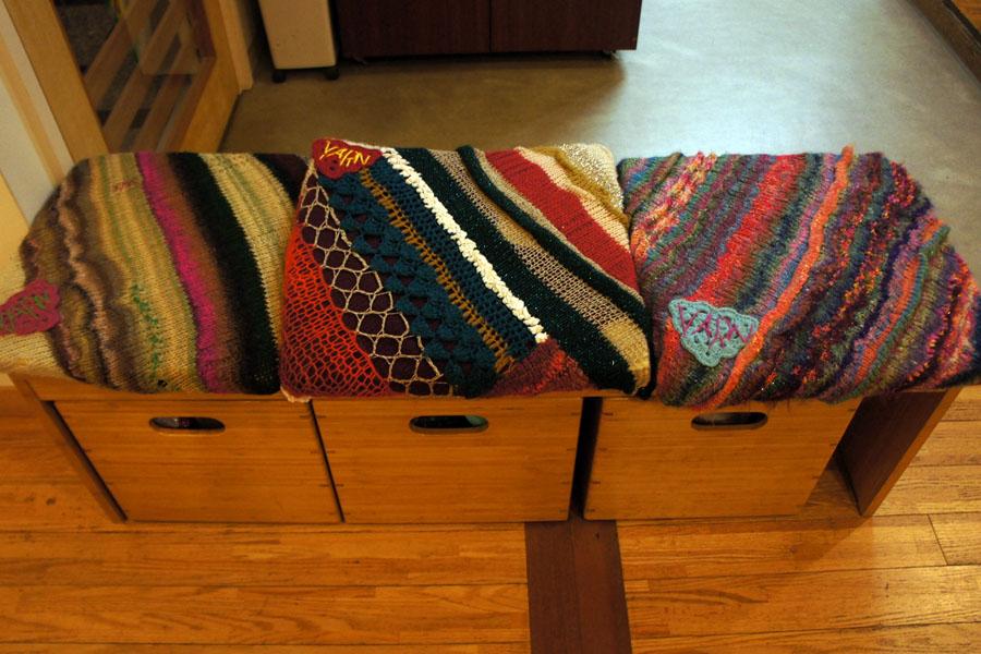 待ち合いのコーヒーマシーンの前には手編みの椅子カバーがかけられたベンチ。