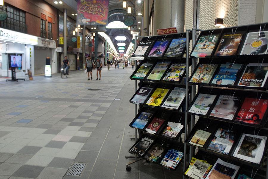 商店街に置かれたチラシラック。月間上映スケジュール「今日なに観よう?」も。